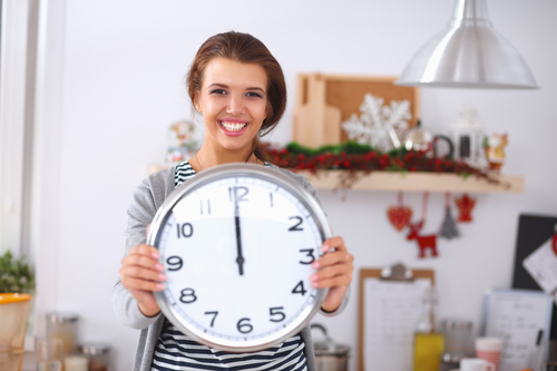 Happy young woman holding clock - maid house cleaning